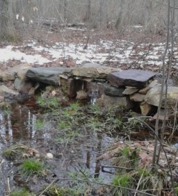 stone bridge crossing a wetland area in rockland town forest