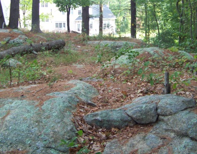 The Mack Trail runs across a rocky outcropping before descending down to the forest.