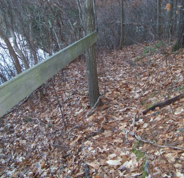 wooden railing pond side on trail at cushing woods
